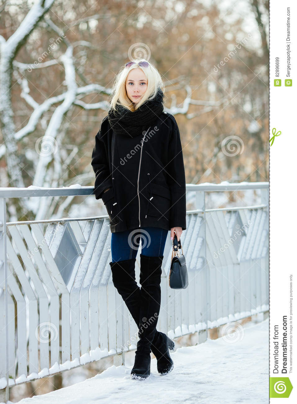Winter portrait: young blonde woman dressed in a warm woolen jacket blue jeans long boots posing outside in a snowy city park
