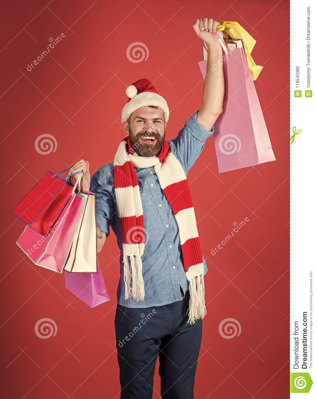 a3b4b5651875e Winter sale. Christmas man shopper smile in santa hat with winner gesture.  Hipster hold shopping bags on red background. New year