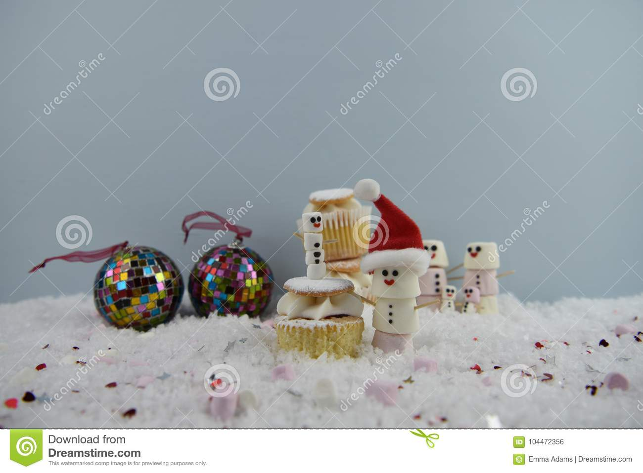 christmas food photography using marshmallows shaped as snowman and standing in snow with cream sponge fairy