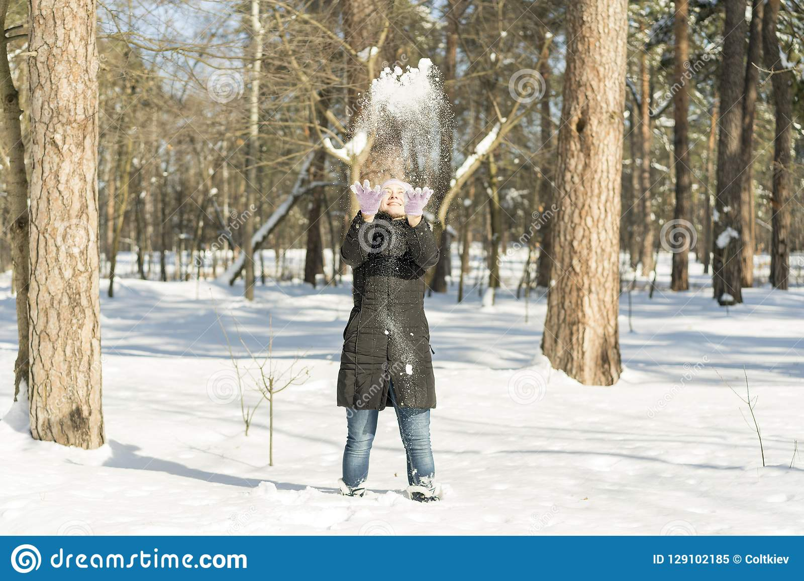 Winter snow fight happy girl throwing snow playing outside. Joyous young woman having fun in nature forest park on snowy day weari