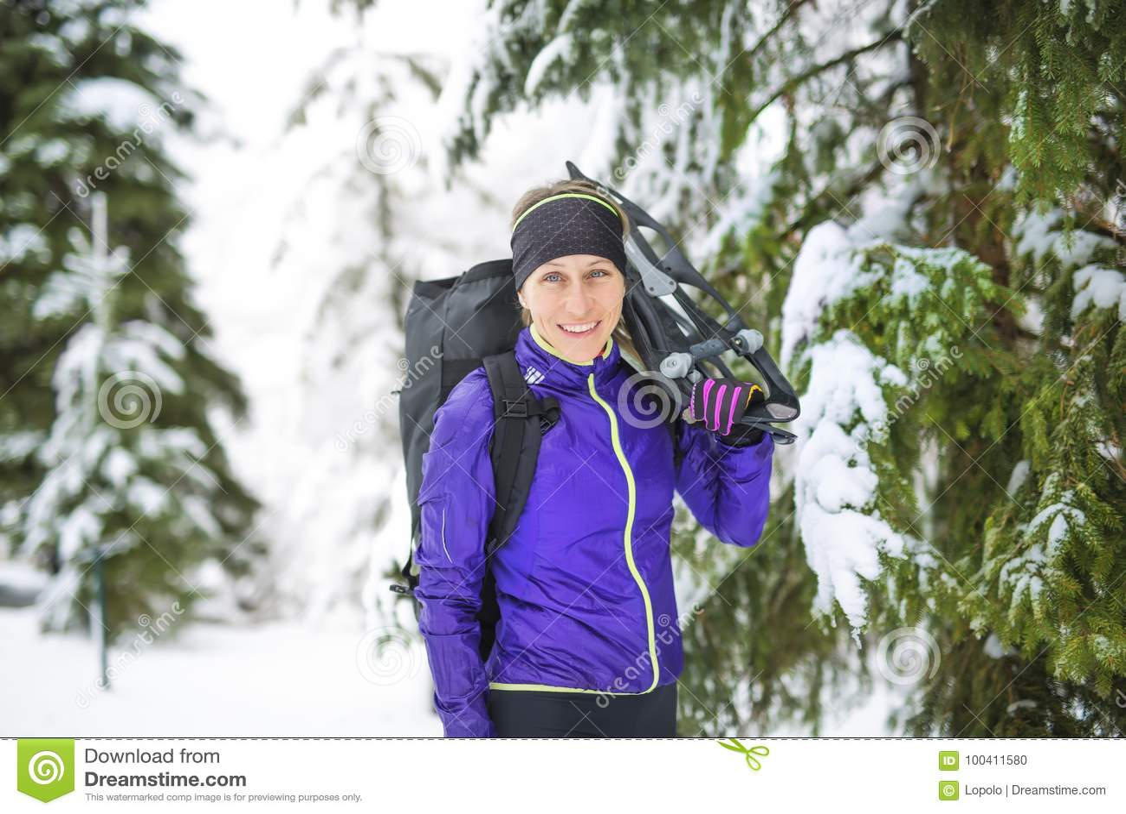 Winter snowshoeing Junger Naturfreundwanderer, der Schneeschuhe draußen im Schnee hält