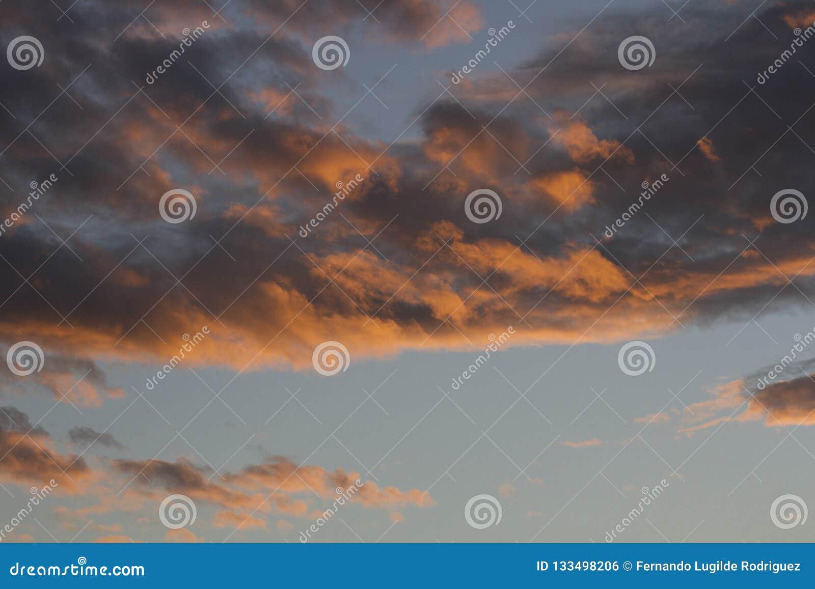 Winter-Sonnenuntergang nachgedacht über flaumige Wolken