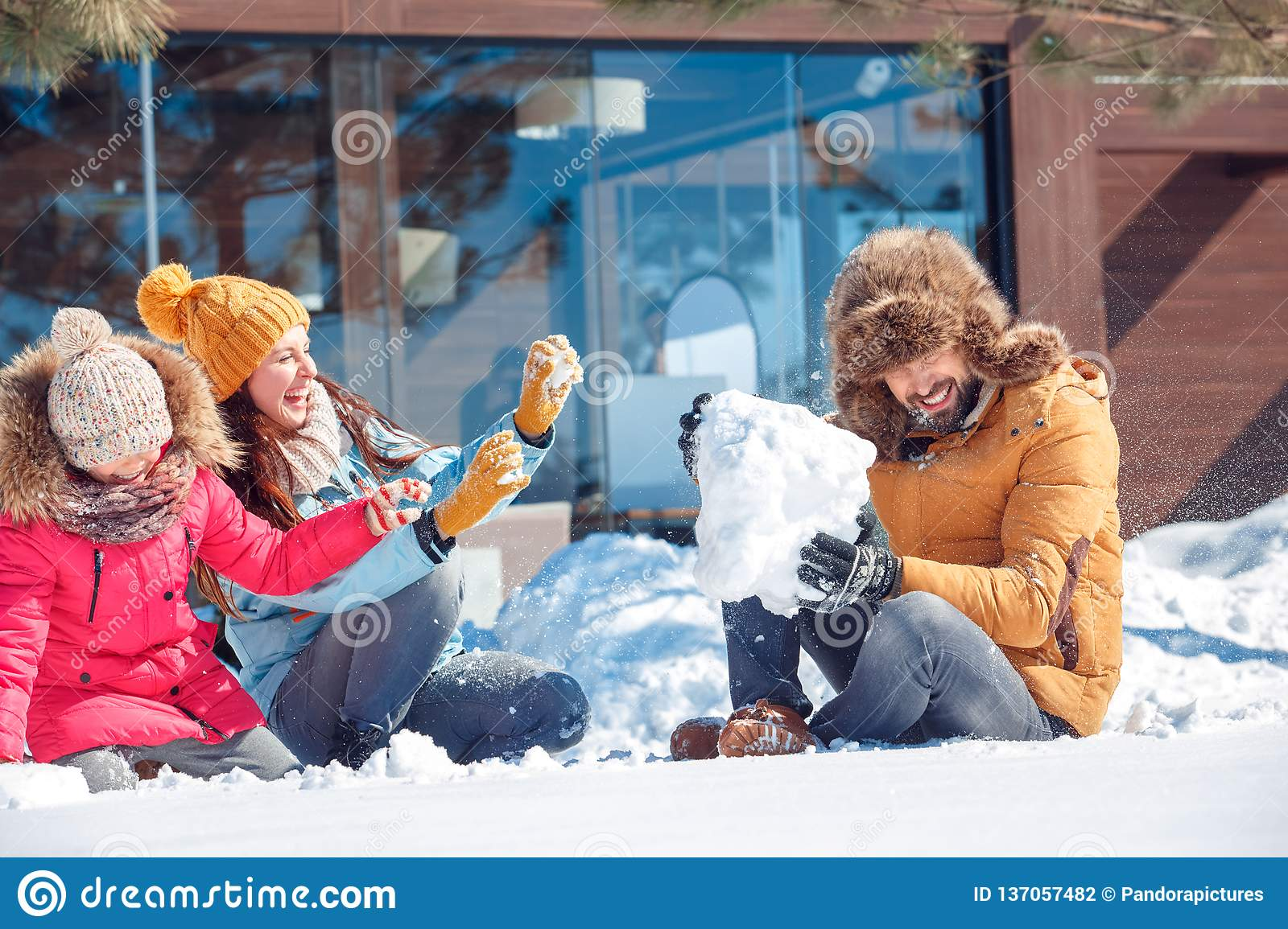 Winter vacation. Family time together outdoors sitting playing with snow laughing cheerful