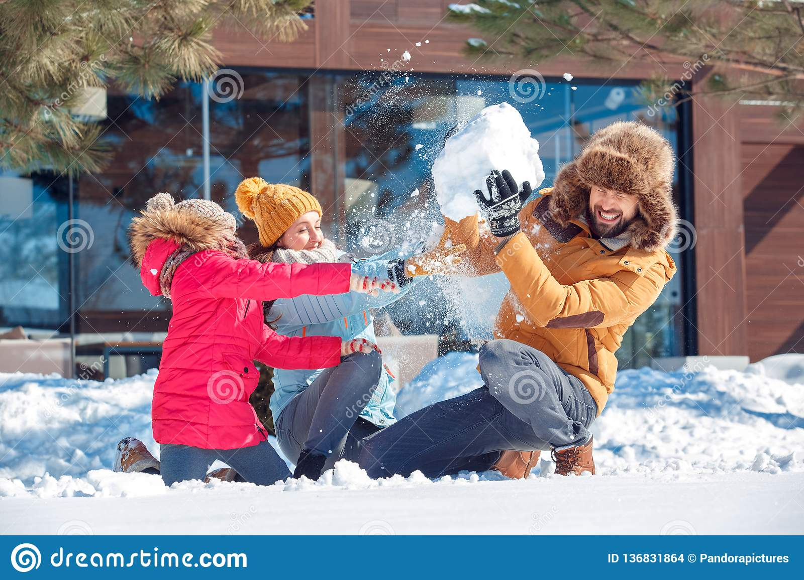 Winter vacation. Family time together outdoors sitting throwing snow fighting laughing surprised close-up