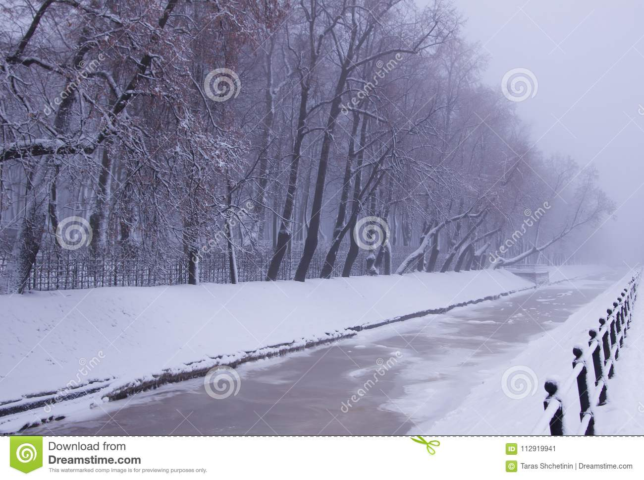 Winter view of frozen Swan Canal on russian sounds `Lebyazhy Canal` and trees covered with snow in the Summer Garden.