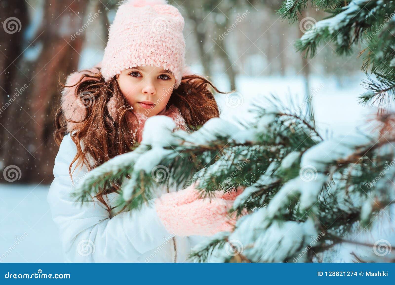 Winterporträt des glücklichen Kindermädchens im weißen Mantel und rosa im Hut- und Handschuhspielen im Freien im Wald des verschn