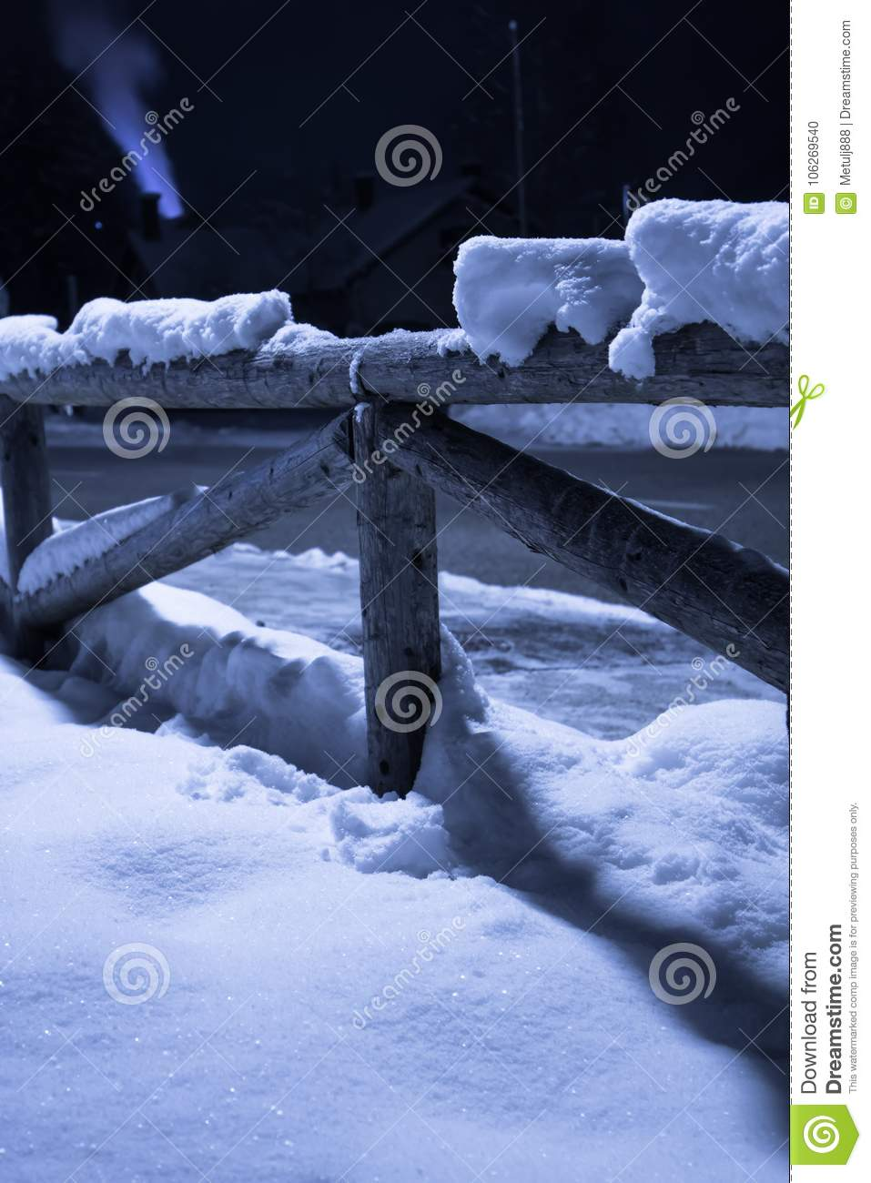 Wintertime fallen snow on wooden fence motif at night with smoke going out the chimney with back light