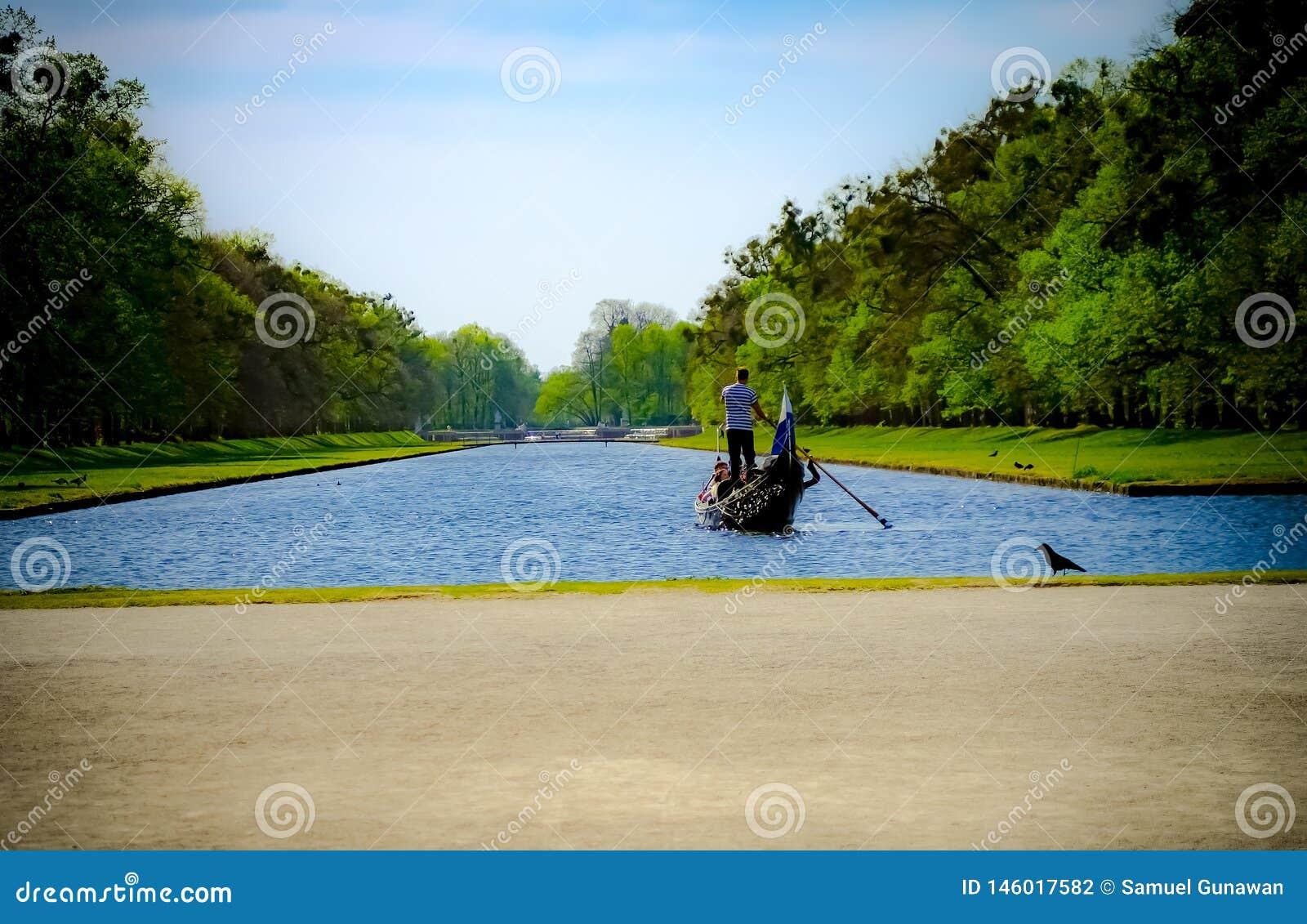 Wiosłujący łódź przecinająca błękitna rzeka