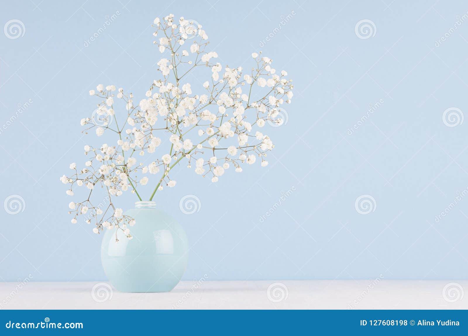 Wiosna bukiet biali mali puszyści kwiaty w błękicie gładzi okrąg ceramiczną wazę na miękkim białym drewno stole i pastelowej błęk