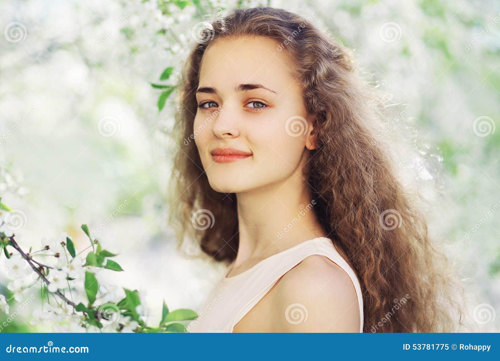 Wiosna portret śliczna dziewczyna z długim kędzierzawym włosy w kwieceniu