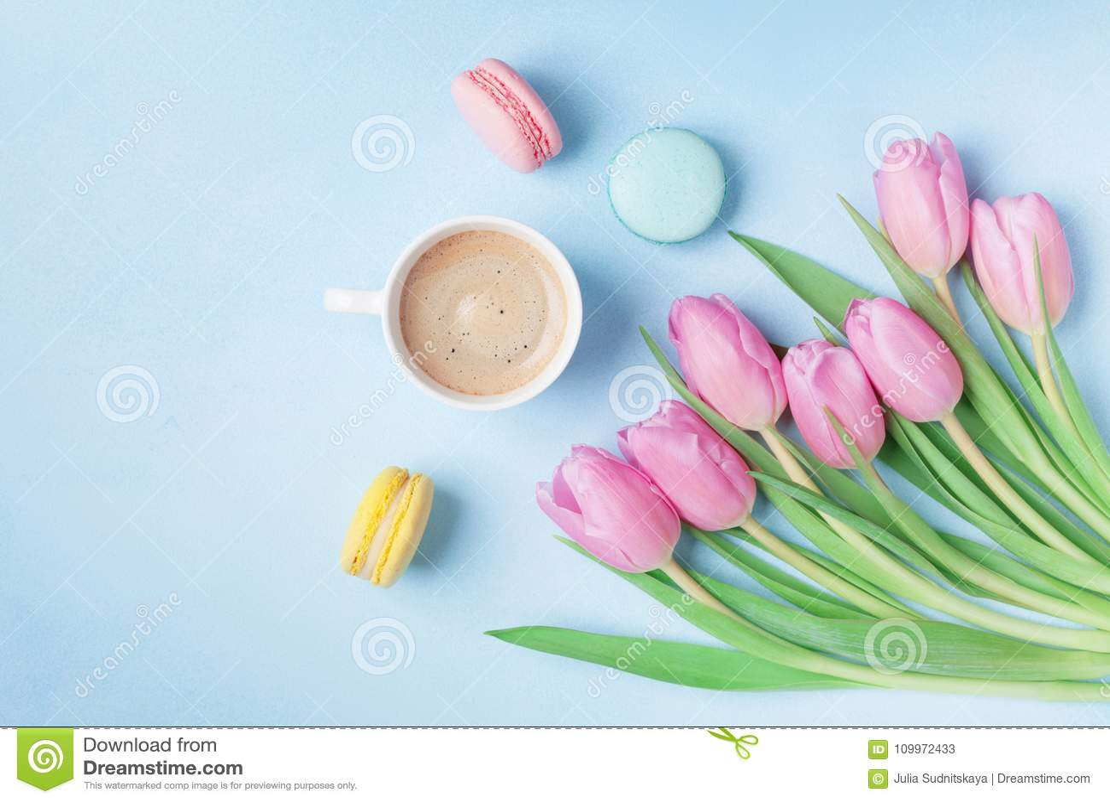 Wiosna tulipanowi kwiaty, kolorowi macaroons i kawa na błękitnym pastelowym stołowym odgórnym widoku, Piękny śniadanie na matek l