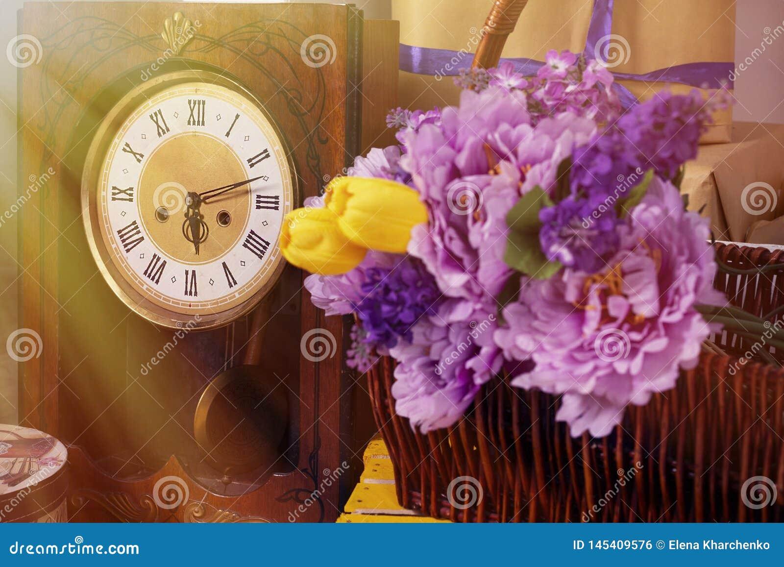 Wiosny fotografia z retro zegarowymi kwiatami w kosza pudełku