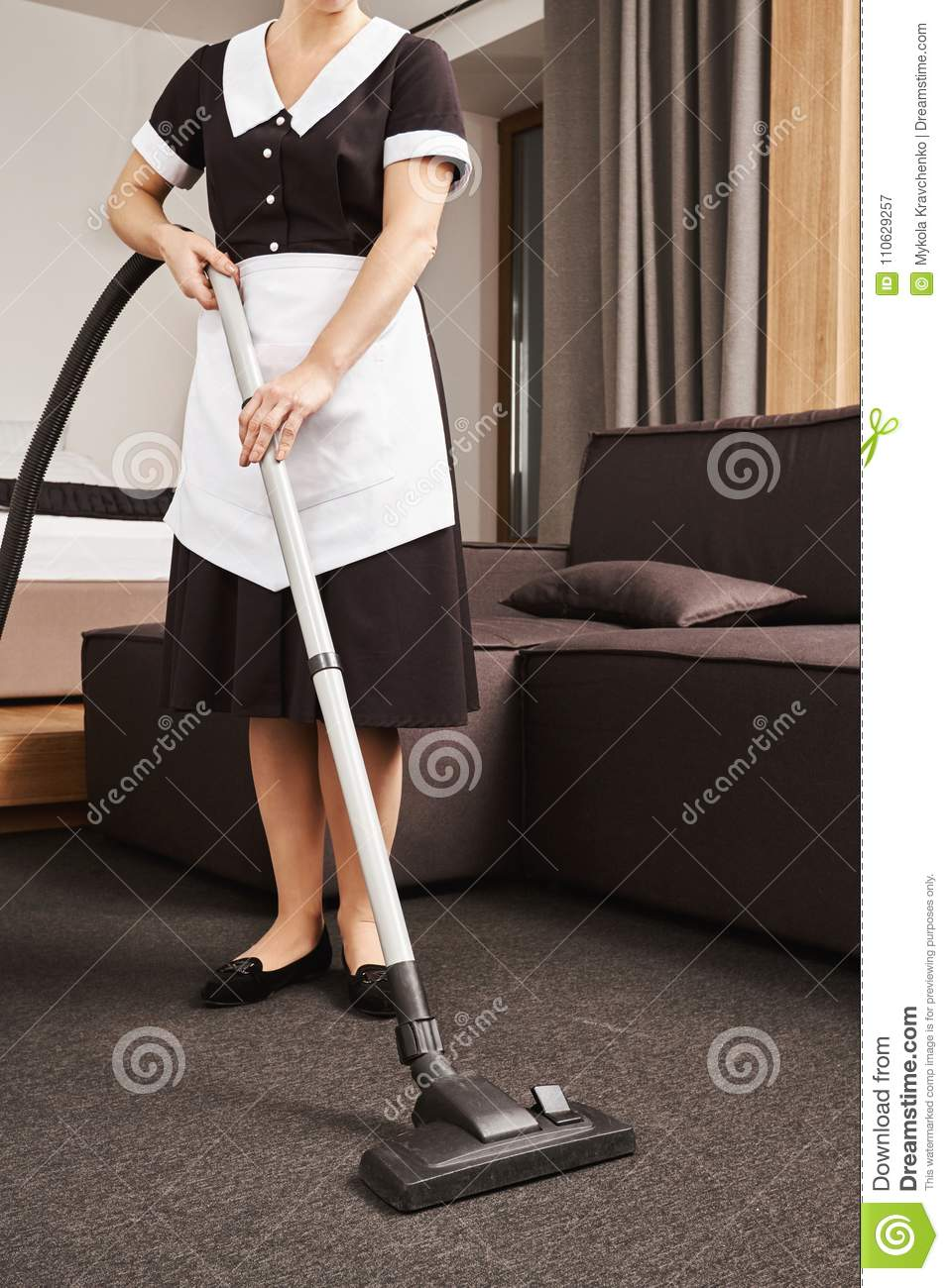 Wipe mess off. Horizontal cropped shot of maid in uniform cleaning living room of employer with vacuum cleaner, removing