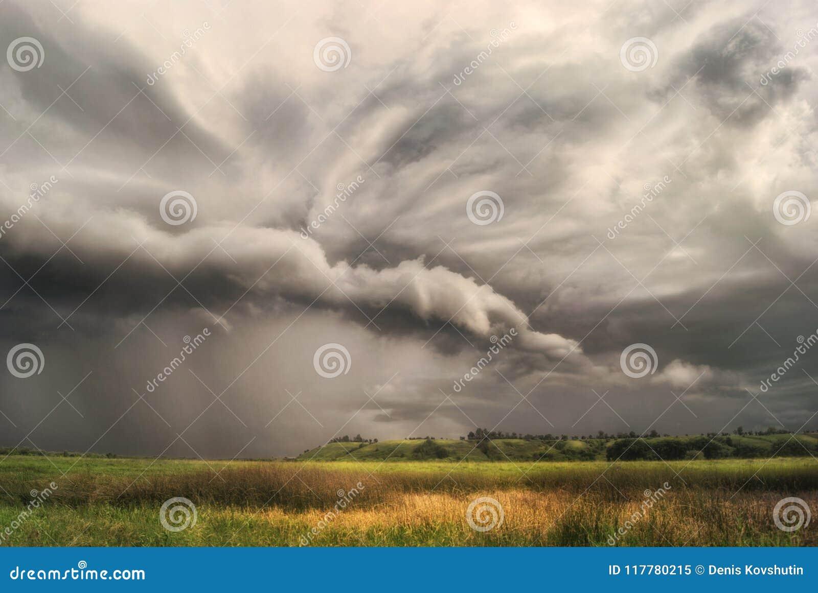 Wirbelsturmsturm über Feldern und Wiesen nähert sich dem hügeligen Tal Regnerischer bewölkter Tag