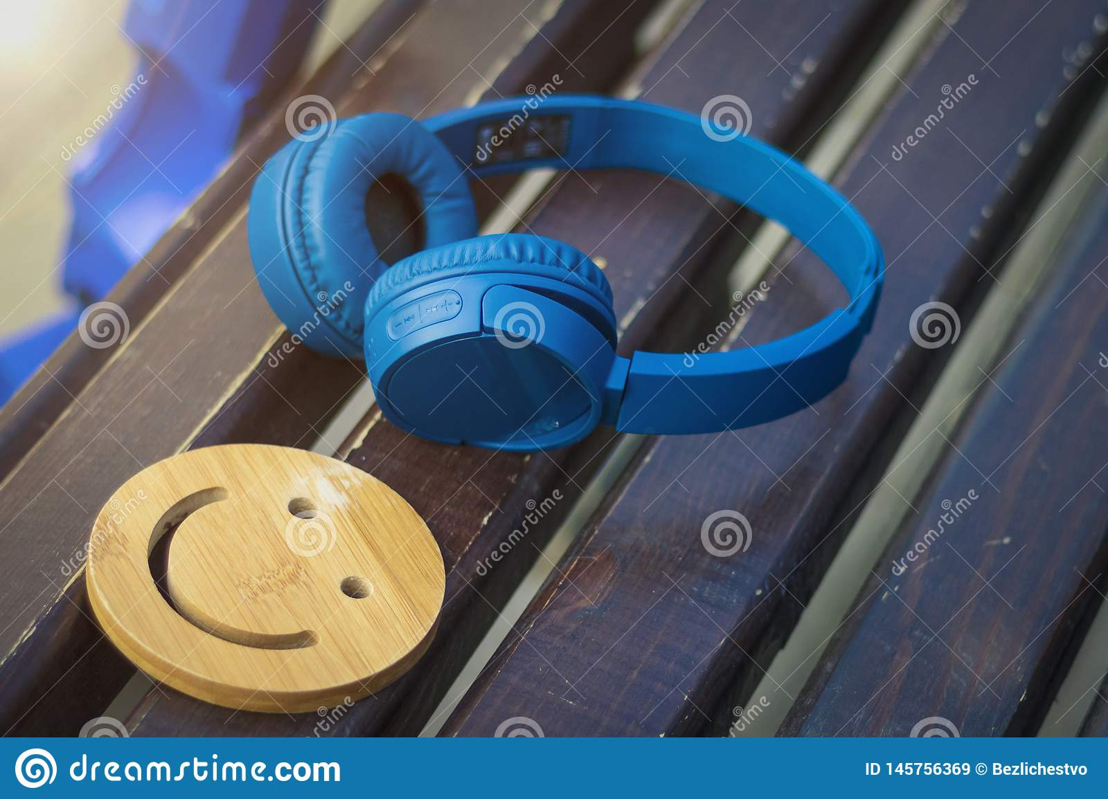 Fine music for perfect mood. Wireless headphones of blue color lie on a dark wooden bench. A smile. The concept of love for music