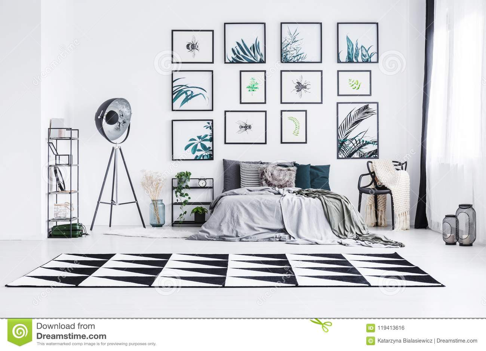 Wirkliches Foto eines Betts, das zwischen einer Lampe und einem Stuhl in einem bri steht