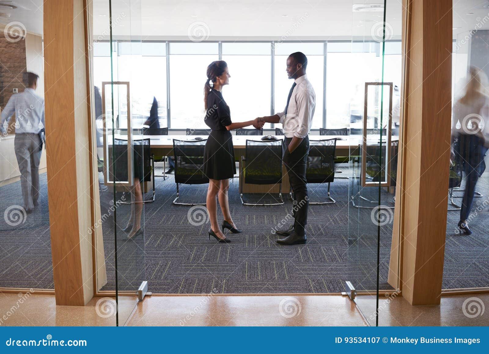 Wirtschaftler, die Hände im Eingang zum Sitzungssaal rütteln