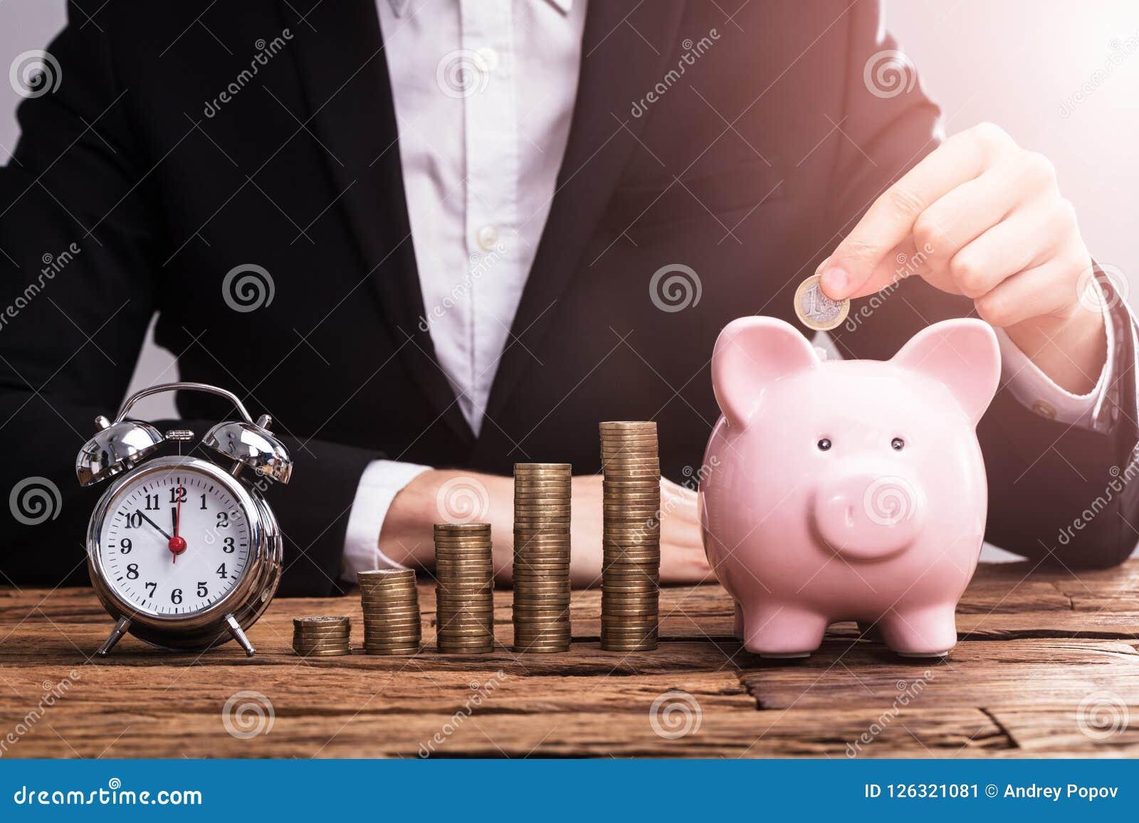 Wirtschaftler ` s Hand, die Münze in Piggybank einsetzt