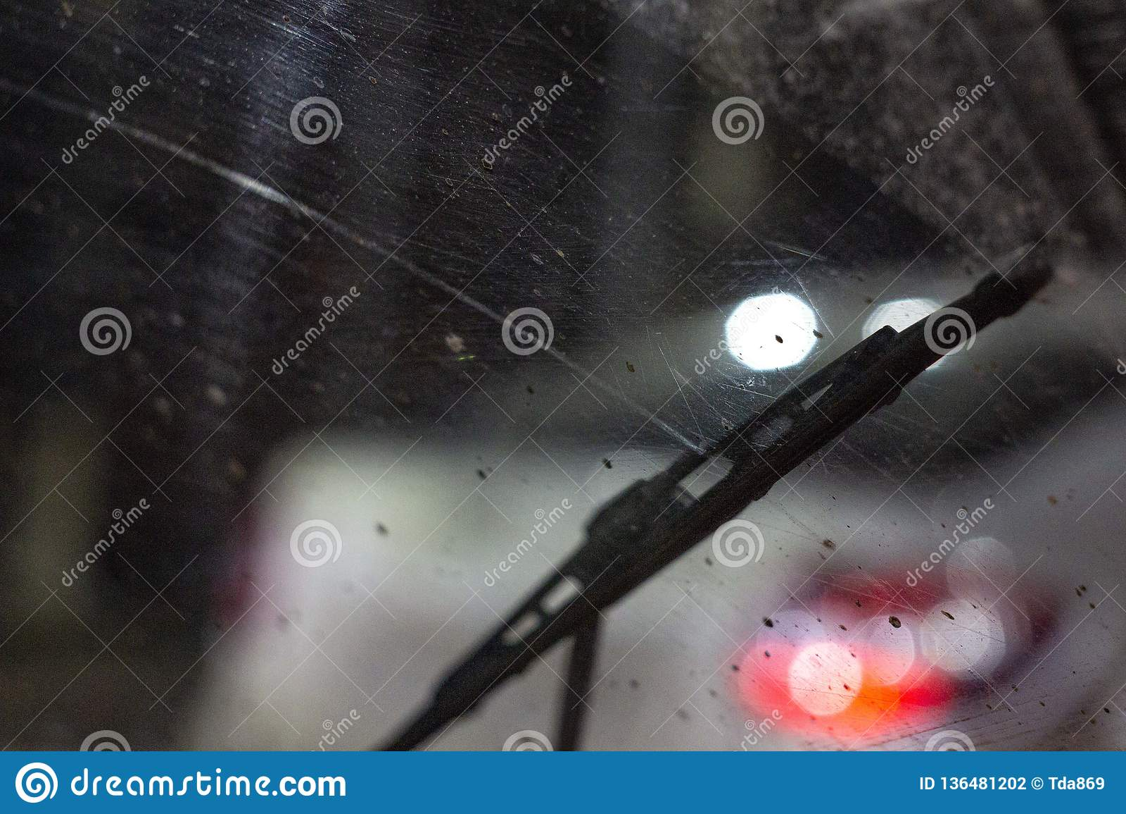 Wischer innerhalb des Autos auf einer schmutzigen verkratzten Windschutzscheibe, Regenjahreszeit, nachts die vorderen und hintere