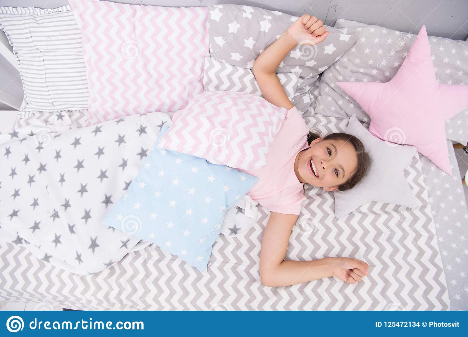 Wish her good morning. Girl child lay on bed her bedroom. Kid awake and full of energy. Pleasant time relax cozy bedroom