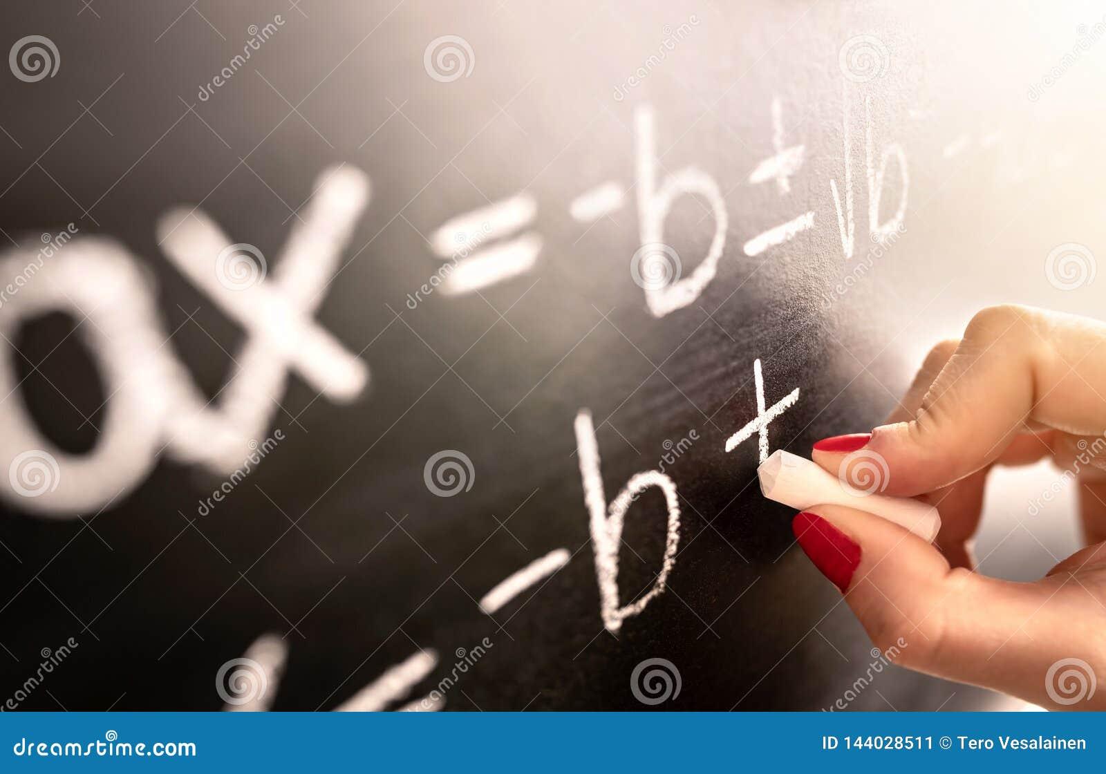 Wiskundeleraar het schrijven functie, vergelijking of berekening op bord in schoolklaslokaal