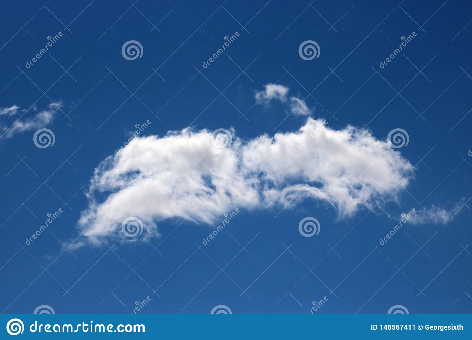 Wispy white cloud against blue sky on a sunny day
