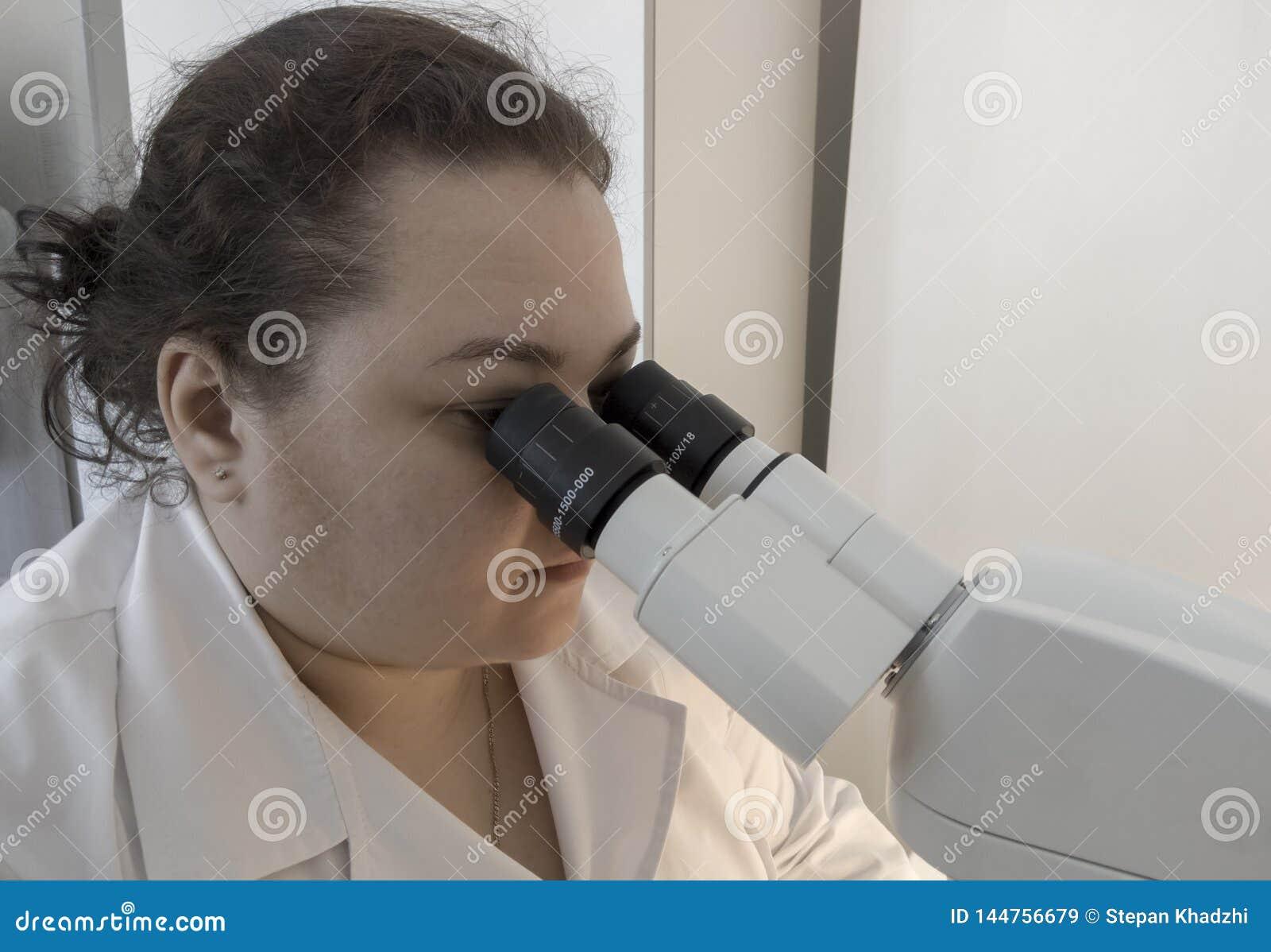 Wissenschaftler, der durch ein Mikroskop in einem Labor tut Forschung schaut