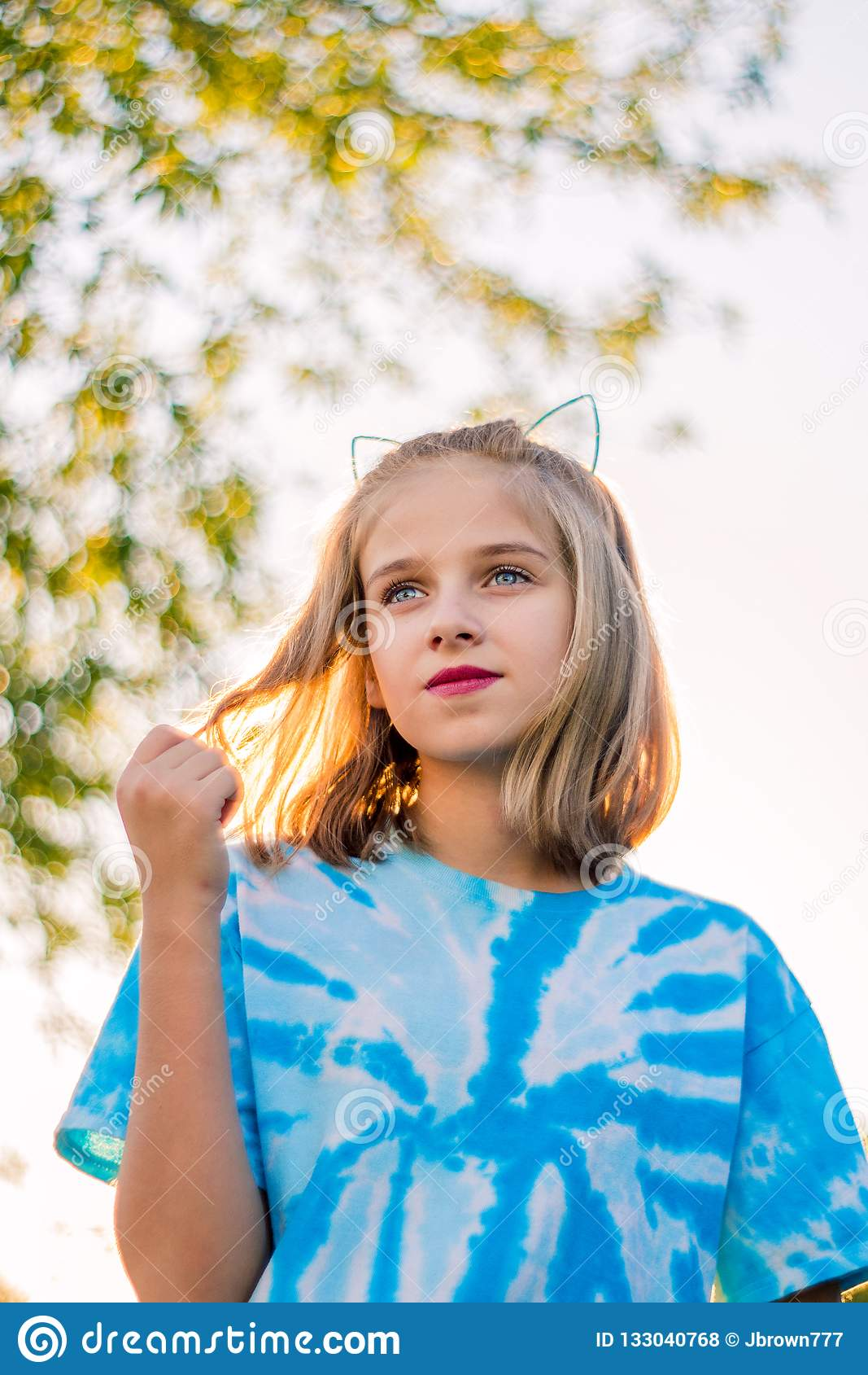 Wistful Nostalgic Image of Young Blond Girl Playing With Hair