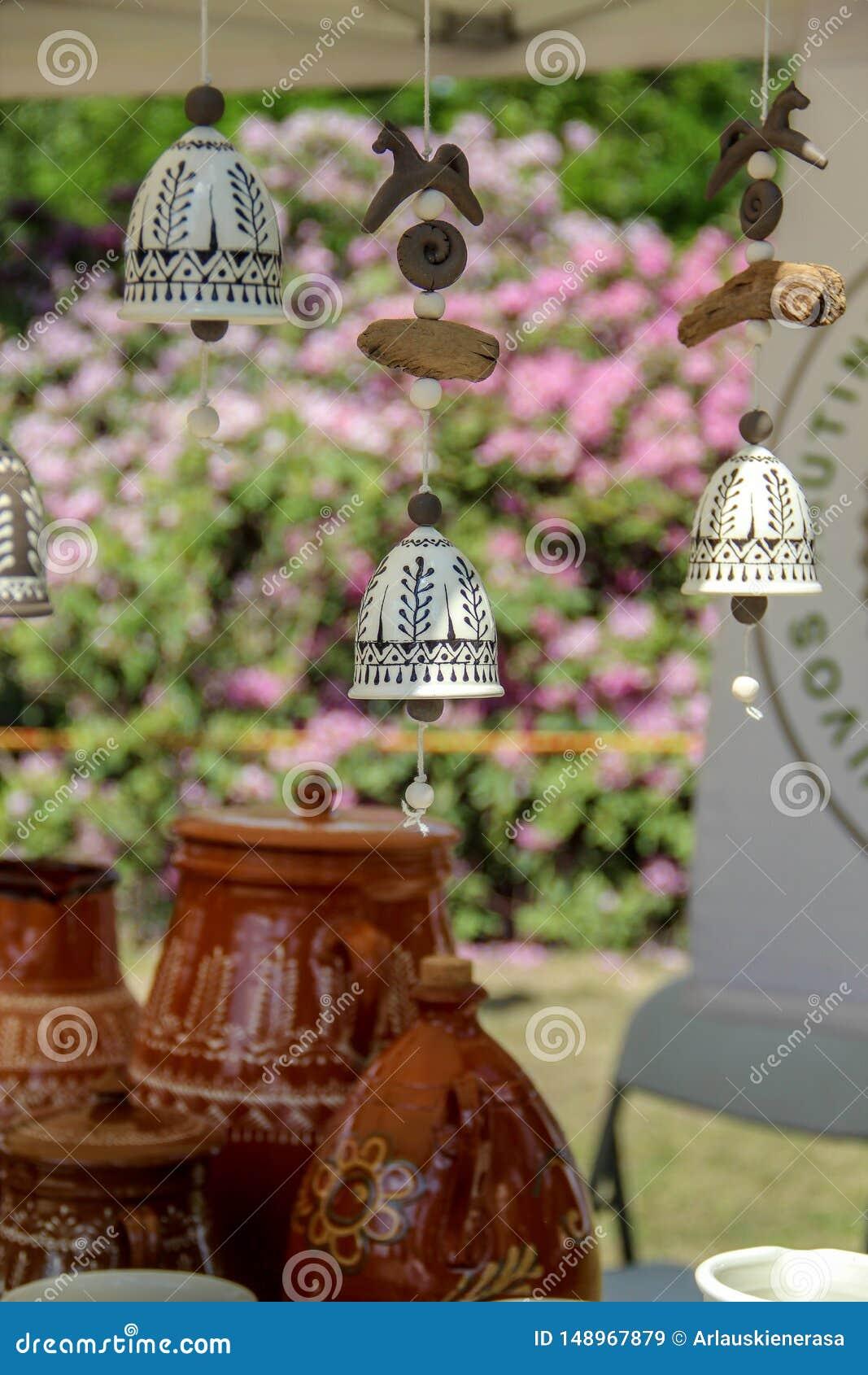 Wisz?cy delikatni handmade ceramiczni dzwony i niekt?re puszkuj? w tle