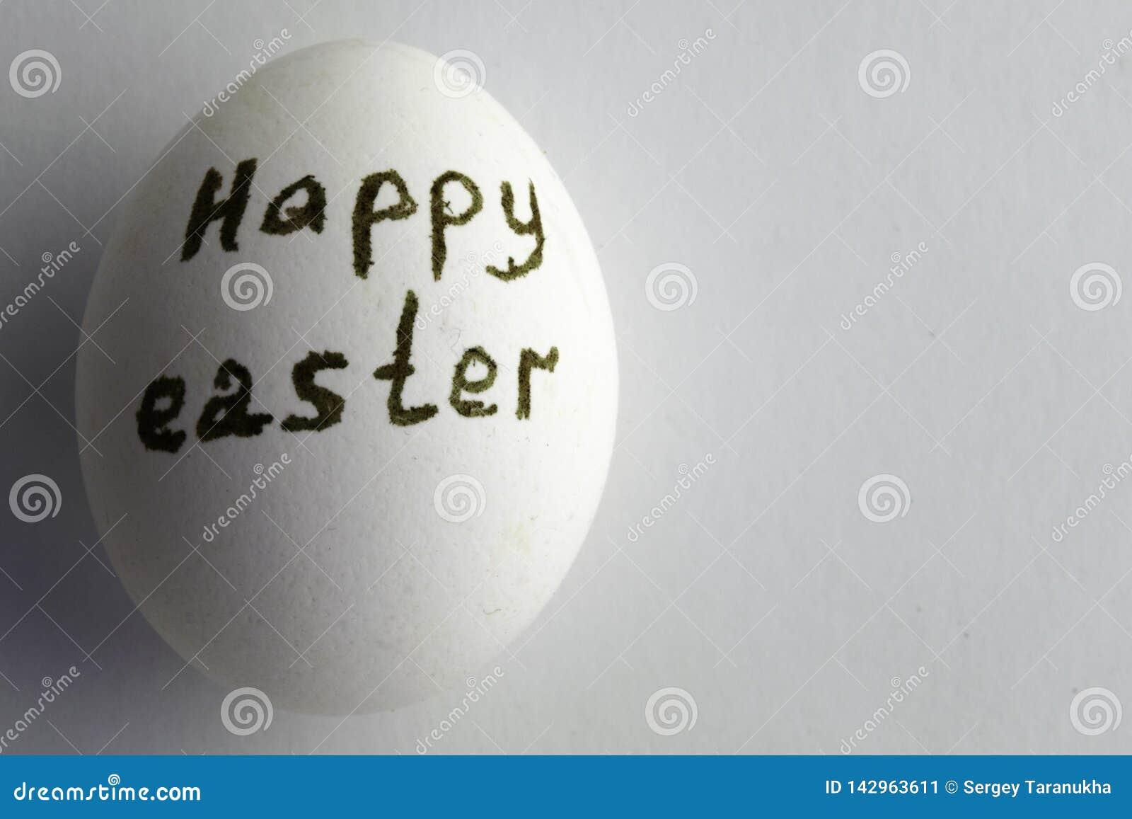 Wit kippenei met de inschrijving gelukkige Pasen op een witte achtergrond, exemplaarruimte