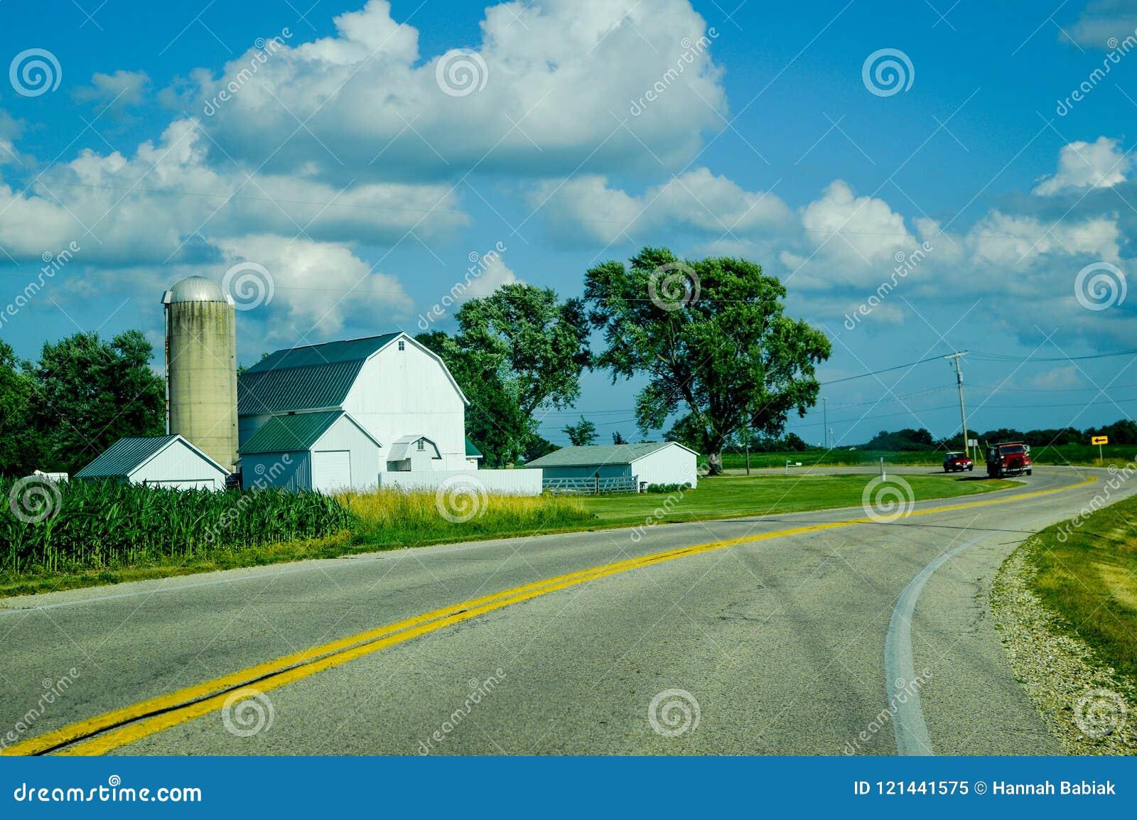 Wit Landbouwbedrijf met Silo op een Curvy-Landweg