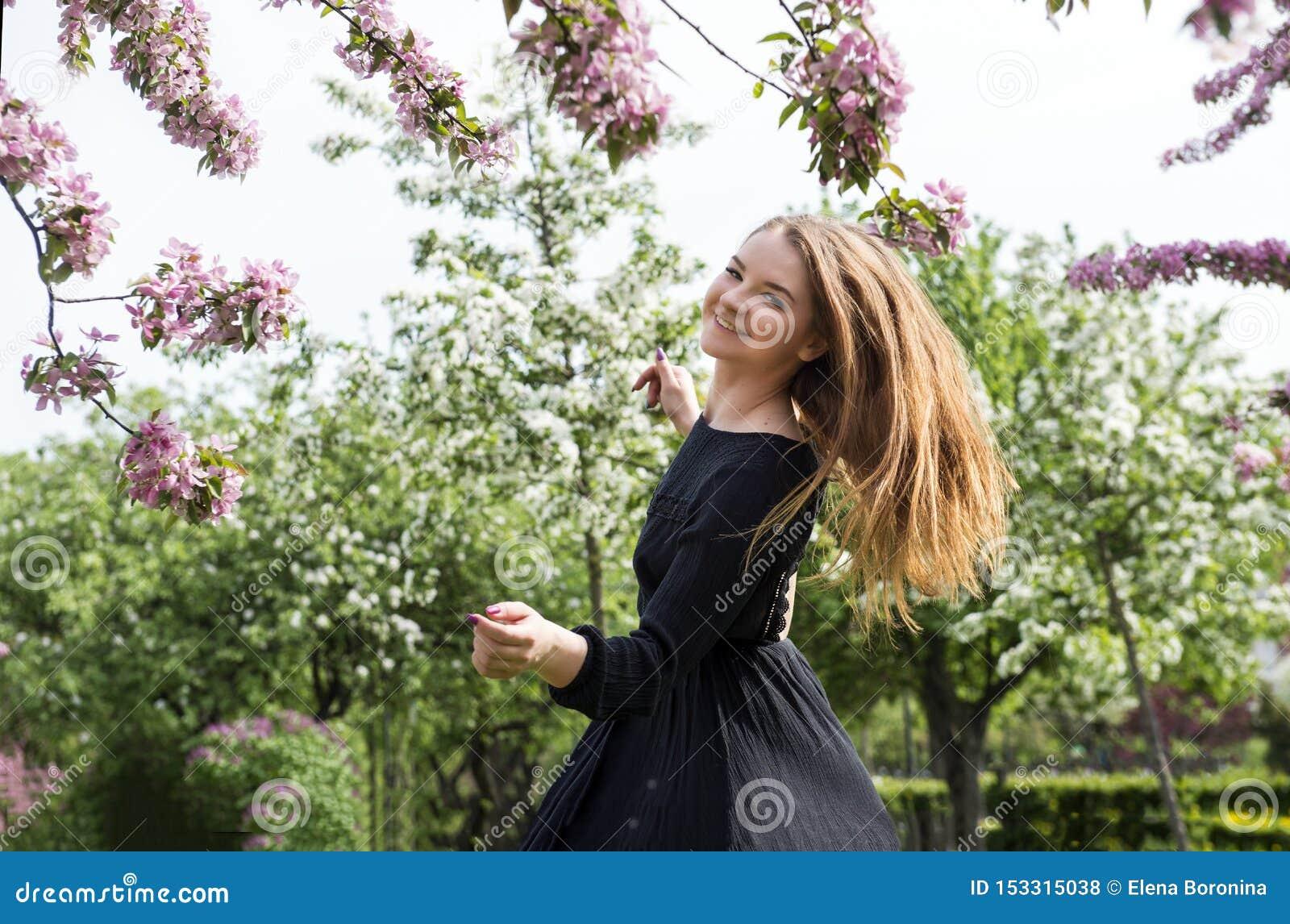 1 wit meisje met lang haar in een zwarte kleding die in een bloeiende Apple-boomgaard, meisje het glimlachen spinnen