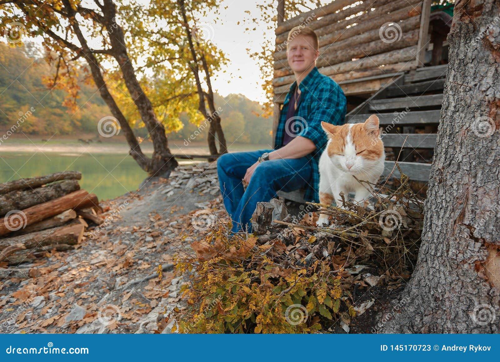 Wit-rode kat in de voorgrond en vage mens op de achtergrond