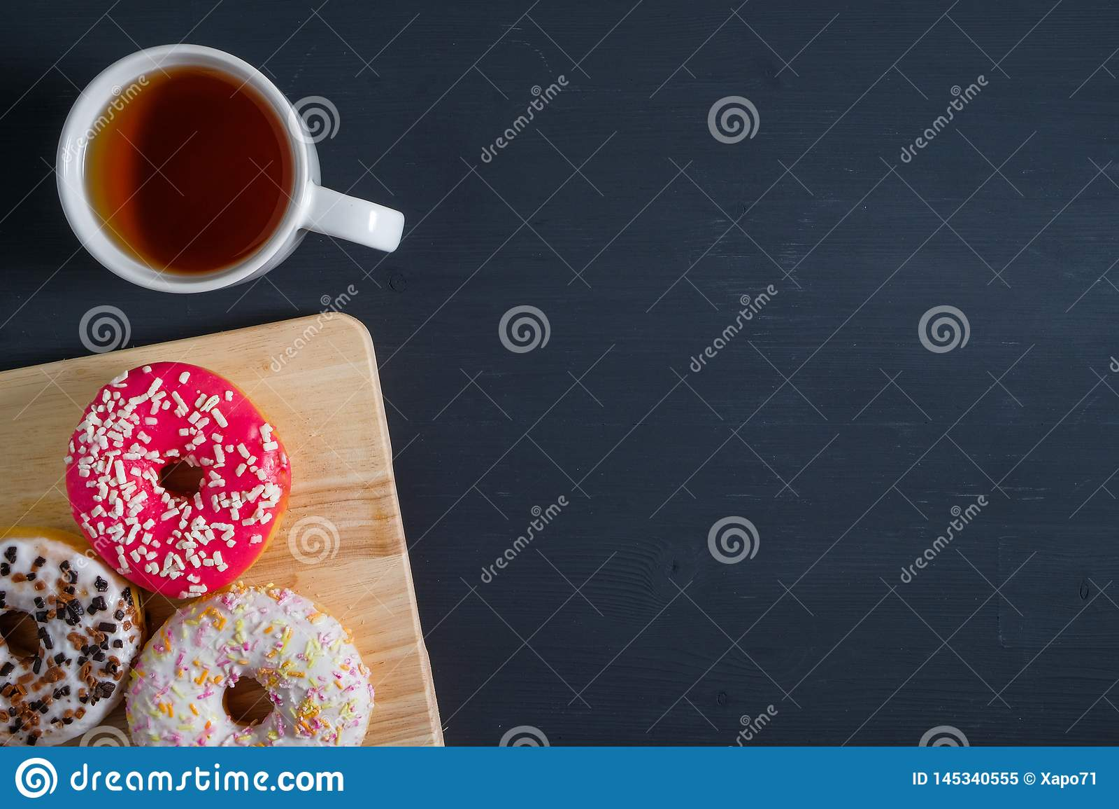 Wit, roze en bruin verglaasd donuts met kop thee in linkerkant op zwarte houten achtergrond