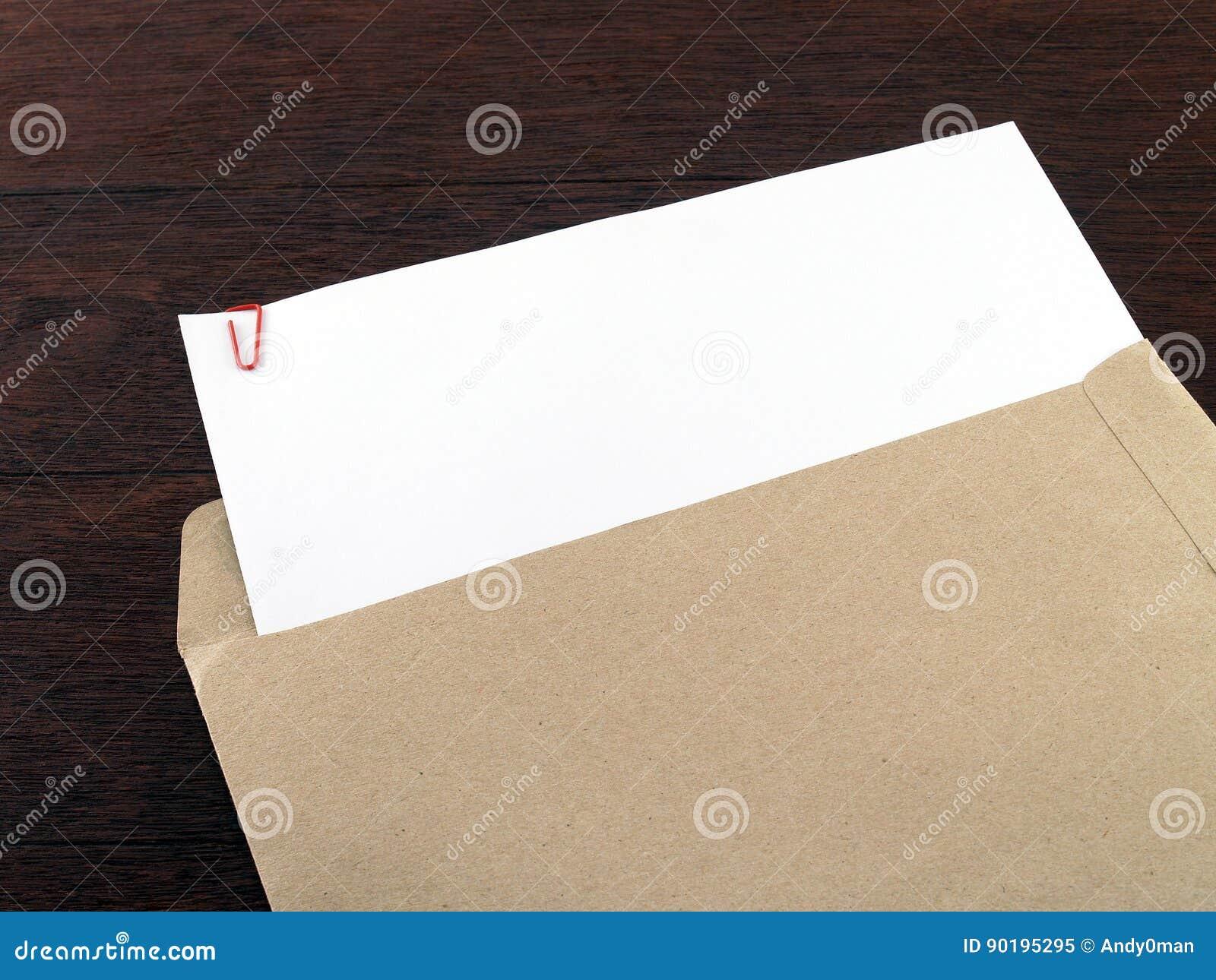 Witboek met paperclip in bruine envelop op donkere bruine houten bureauvloer