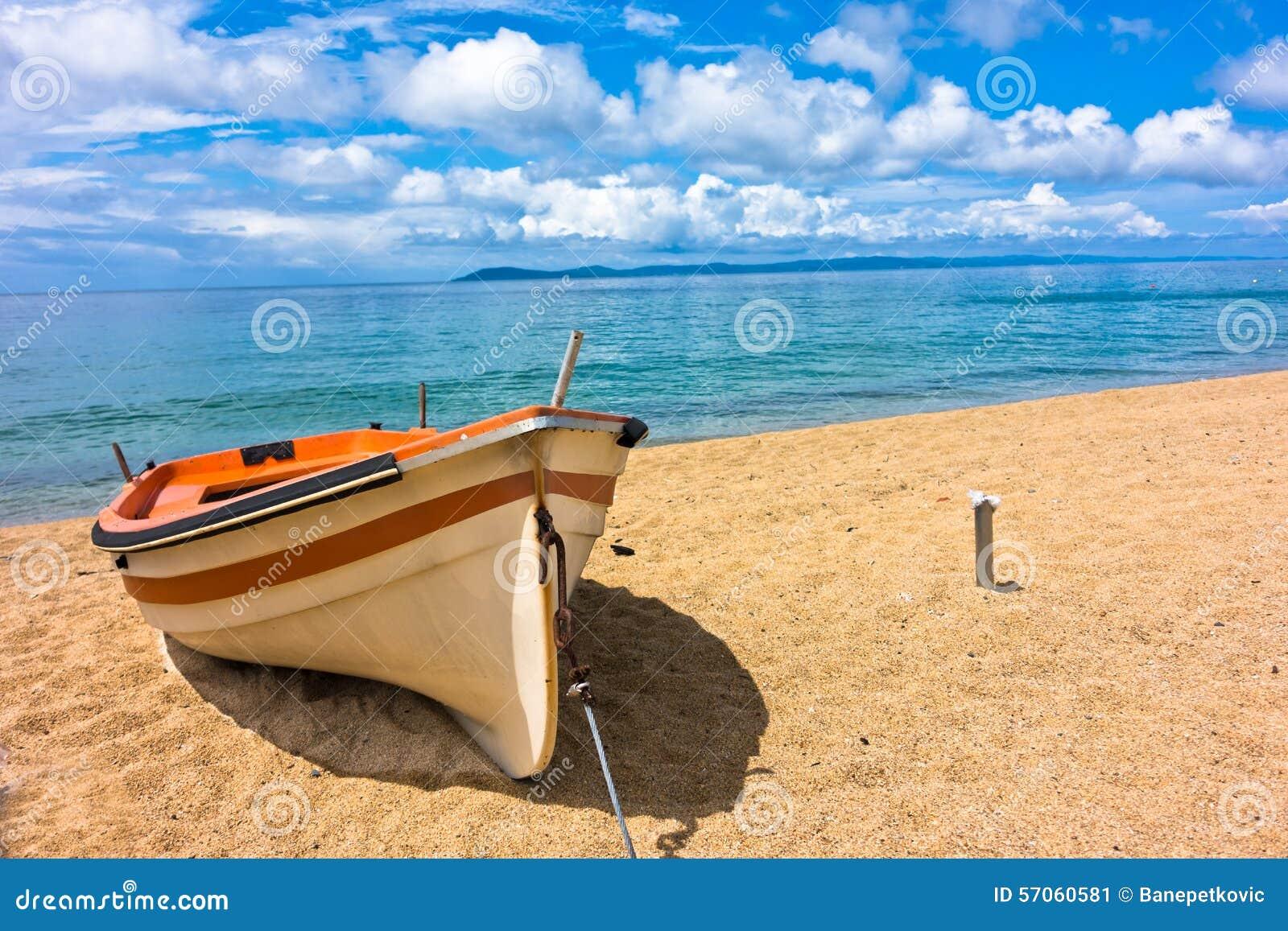 Witte boot op een zandig strand bij ochtend, westkust van Sithonia