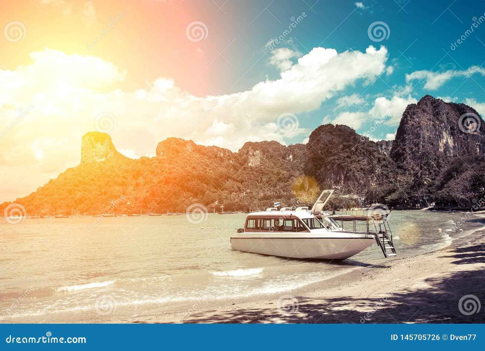 Witte de motorboot wachtende passagier van de luxemotor op de kust van een tropisch eiland Binnen vastgelegd op een zandig strand