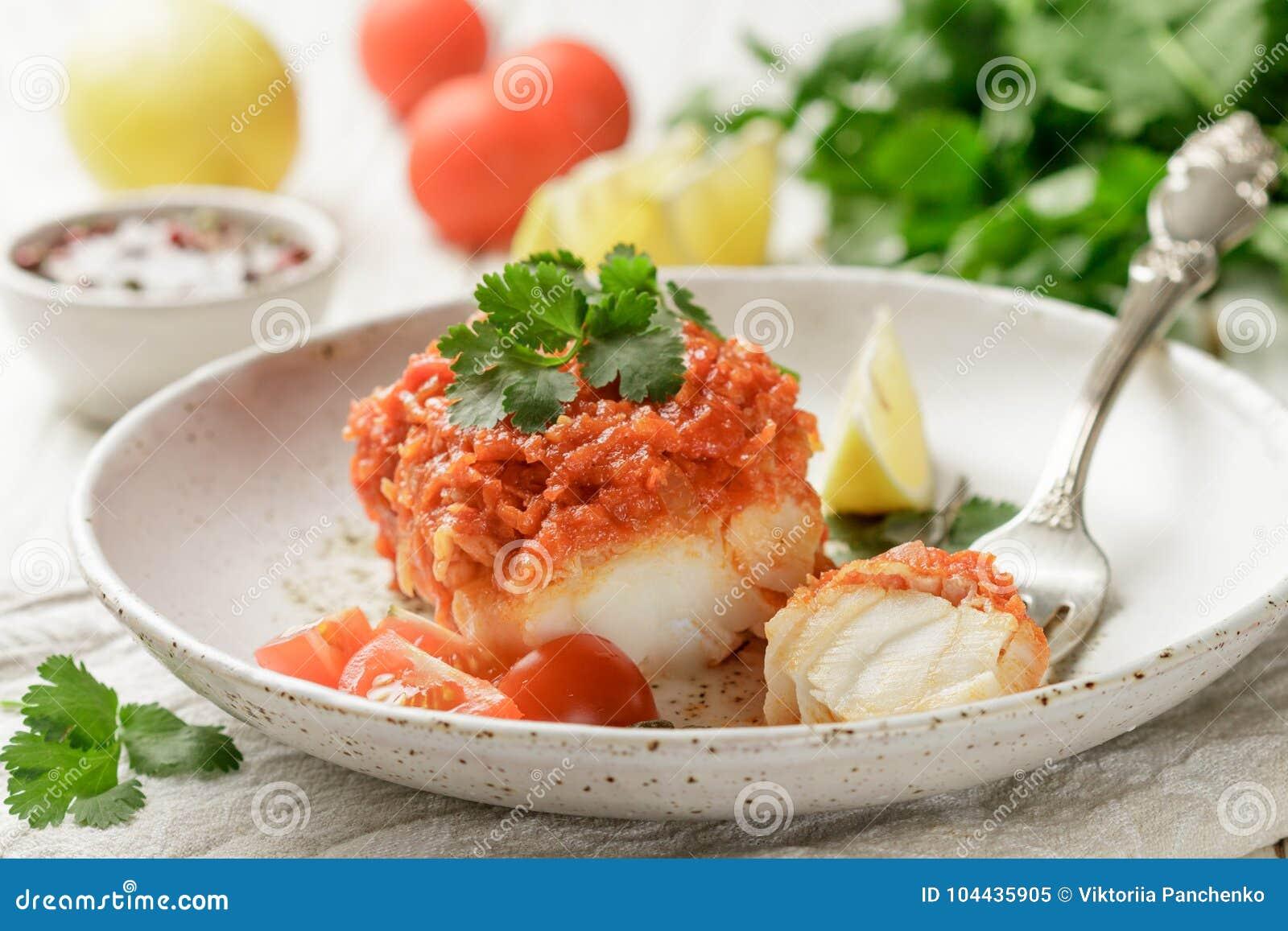 Witte die vissenkabeljauw, Pollock, nototenia, stokvissen, met uien, wortelen en tomaten worden gesmoord