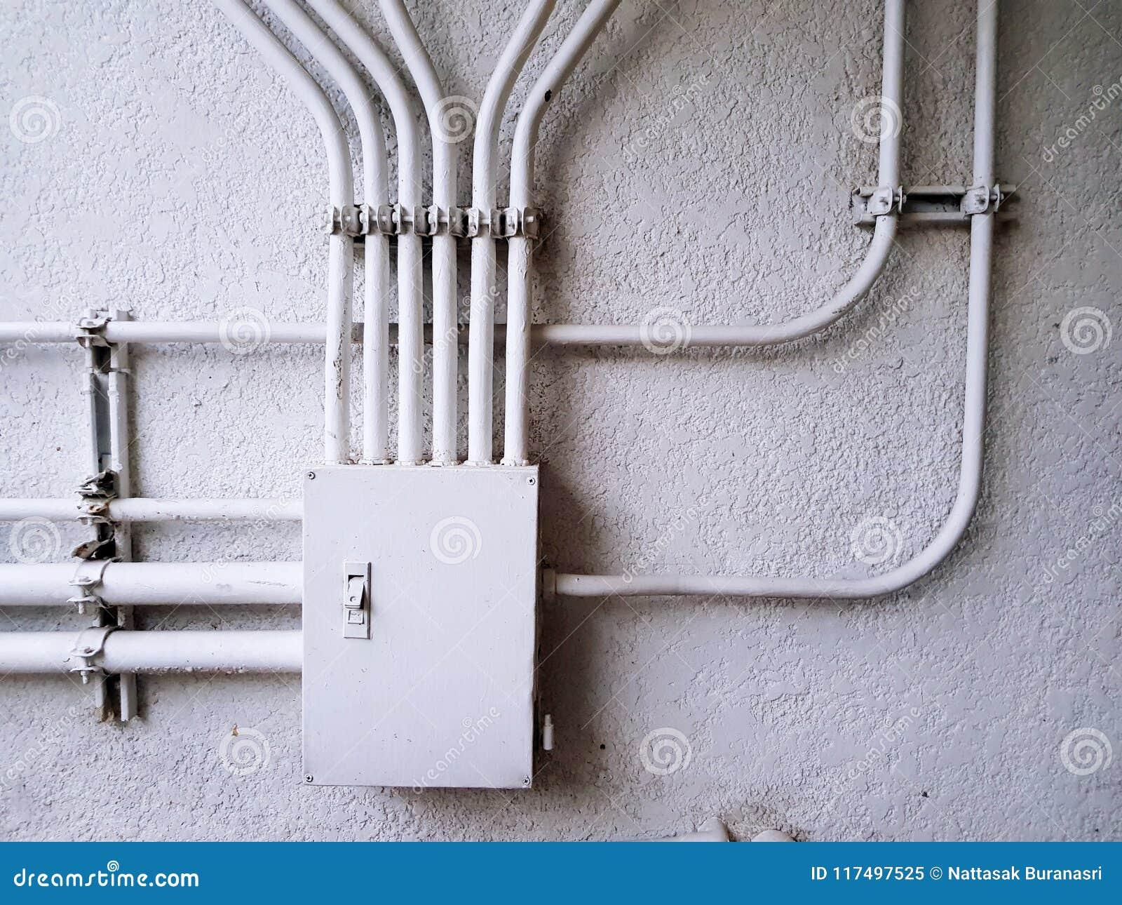 Witte elektrocontrolekabeldoos voor de lijn van de distributiemacht op de witte concrete muur met exemplaarruimte