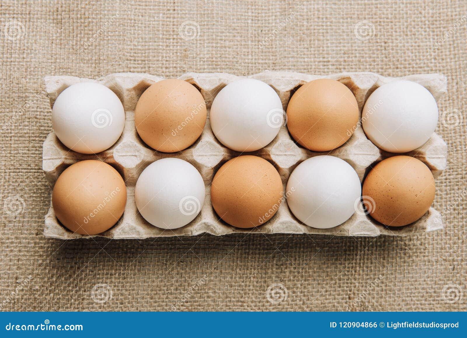Witte en bruine eieren die in eikarton leggen