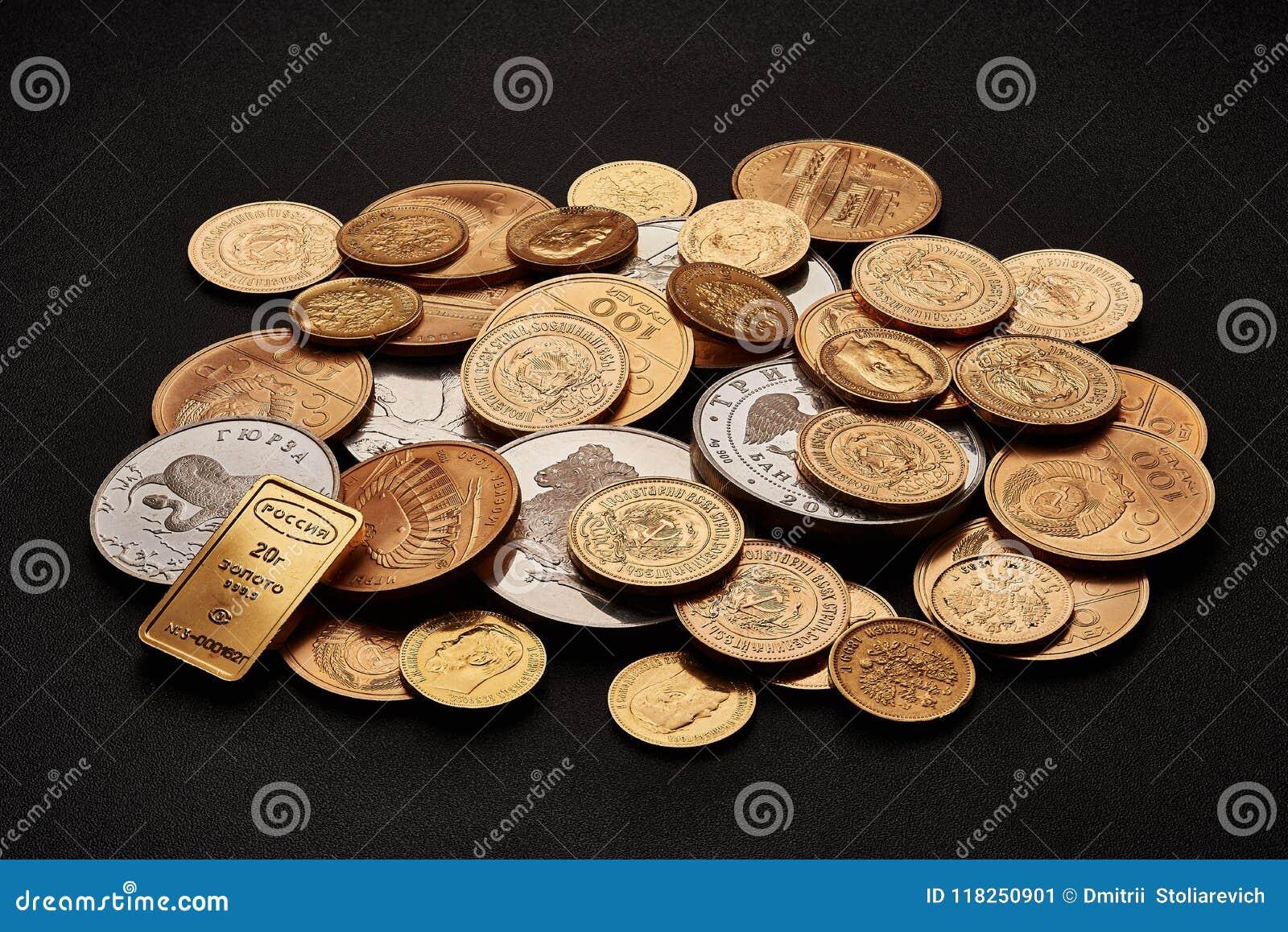 Witte en gele die goudstaven en muntstukken op zwarte achtergrond worden geïsoleerd