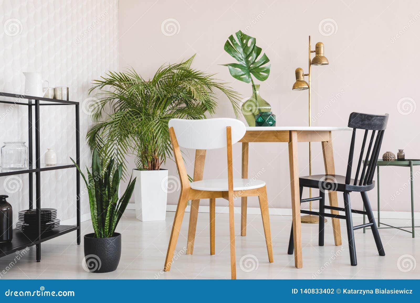 Witte en zwarte stoel bij houten lijst in eetkamerbinnenland met installaties en gouden lamp Echte foto