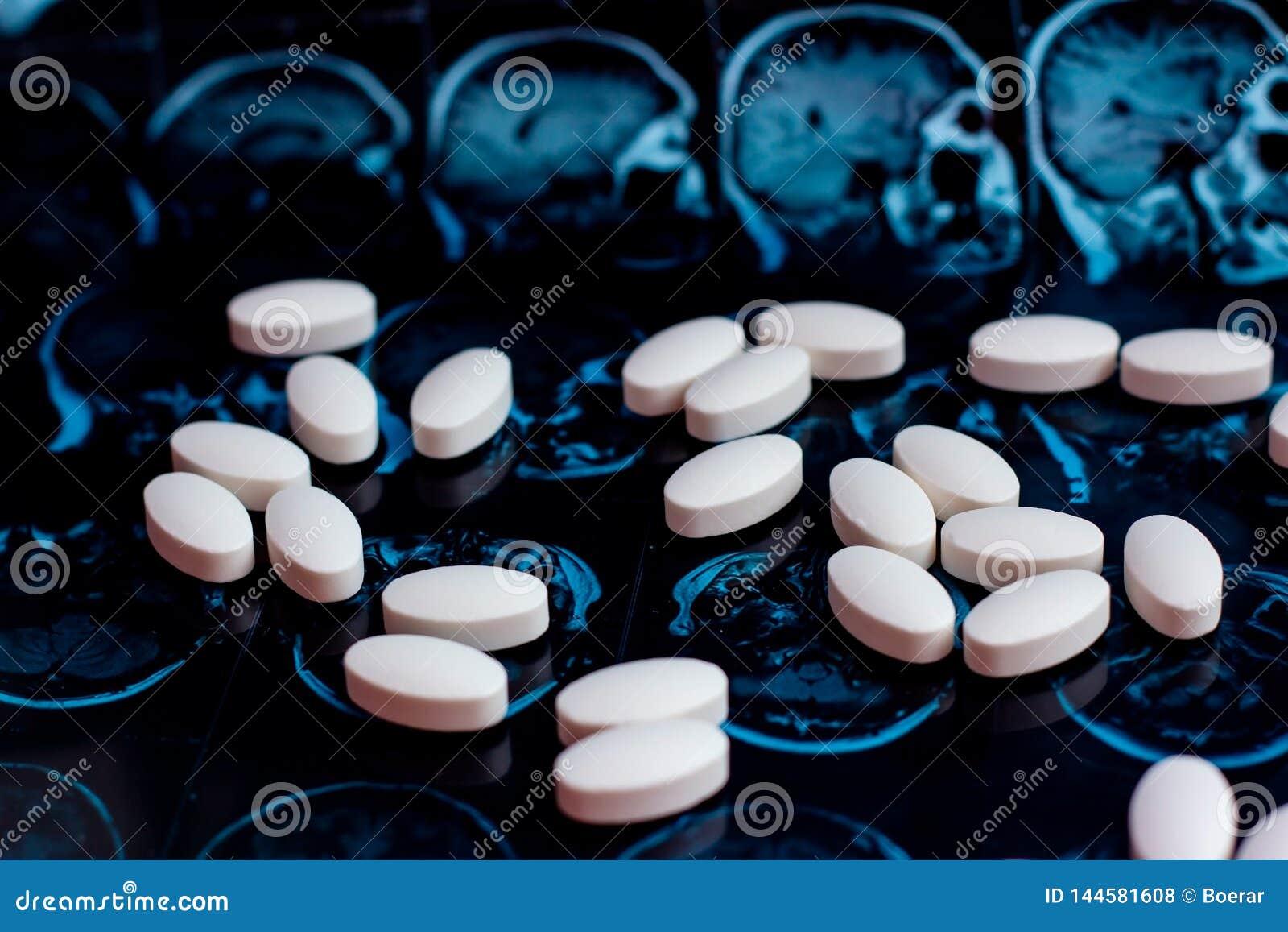 Witte farmaceutische geneeskundepillen op de magnetische achtergrond van het aftastenmri van de hersenenresonantie Apotheekthema,