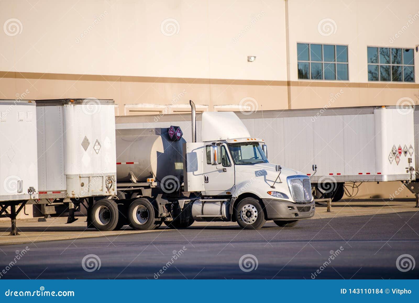 Witte grote de cabine semi vrachtwagen van de installatiedag met tank semi aanhangwagen die zich in pakhuisdok bevinden met een a