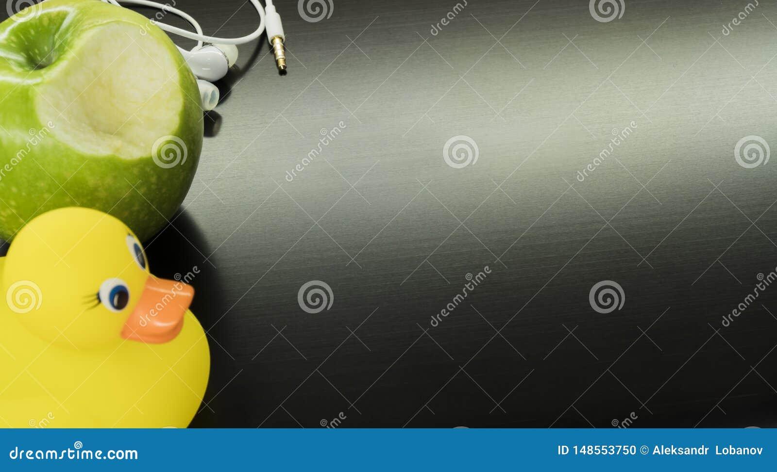 Witte hoofdtelefoons, een gele eend en een groene appel