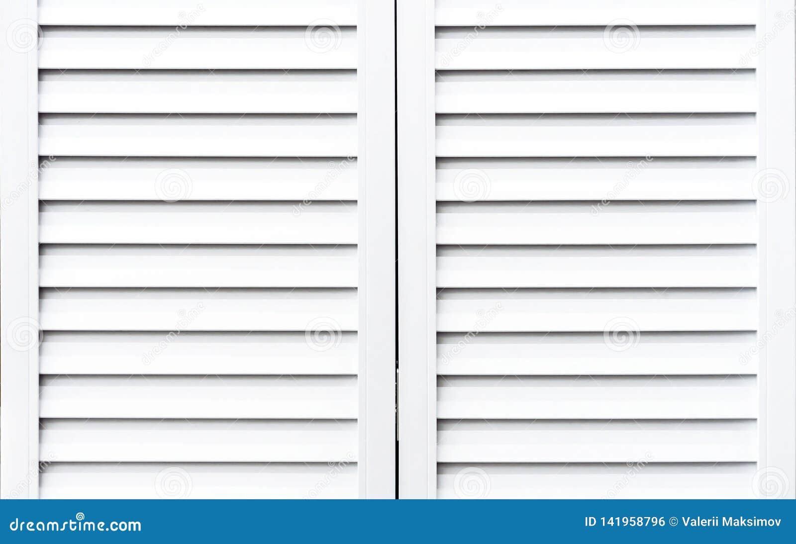 Witte houten blinden om vensters tegen zonlicht te beschermen