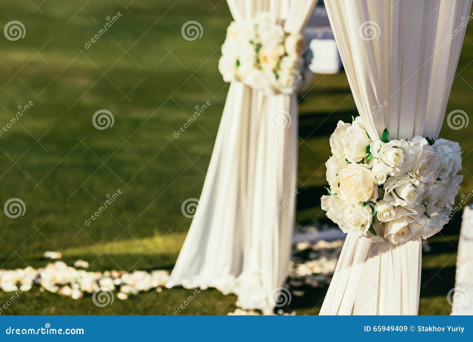 Witte huwelijksboog met bloemen op zonnige dag in ceremonieplaats