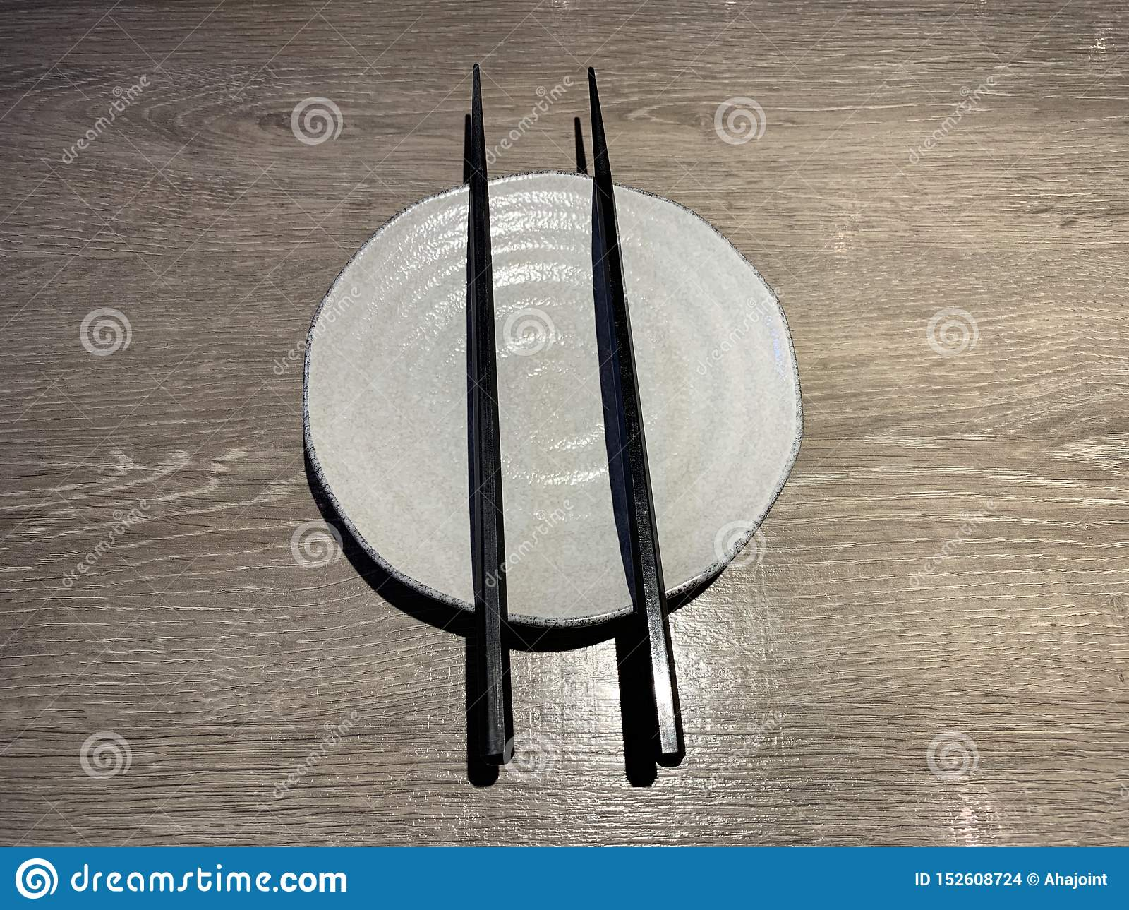 Witte Japanse schotel met eetstokje op houten lijst