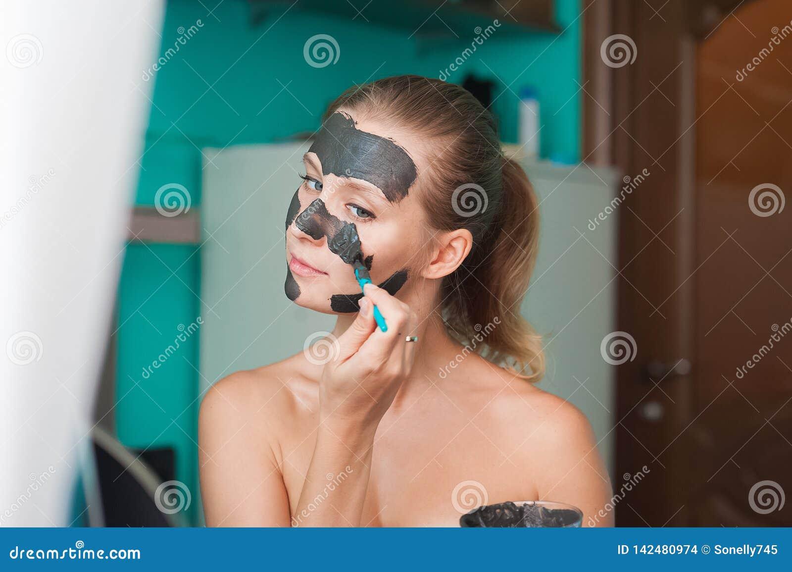 Witte jonge vrouw die een gezichtsmasker thuis op een turkooise achtergrond dragen Europese vrouw in zwart masker voor gezichts d