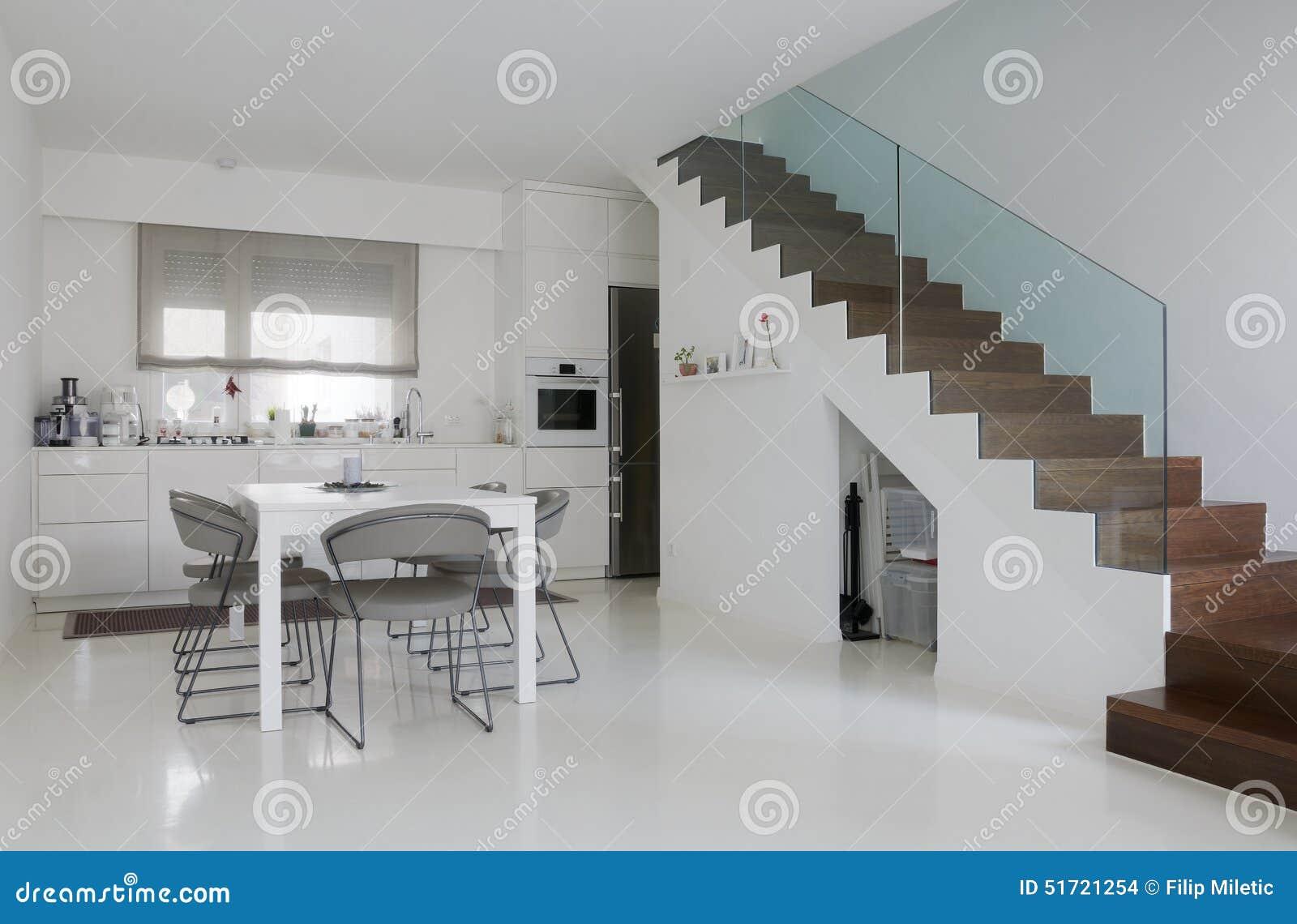Witte keuken en eetkamer met witte epoxyvloer en houten treden.